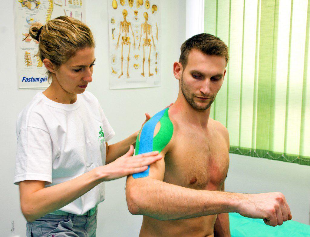 férfi vállára kineziológiai tapaszt ragasztó orvos
